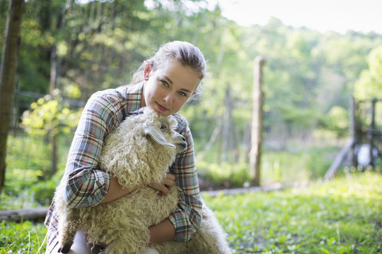 A Teenager Kneeling And Putting Her Arms Around A Very Curly Haired Angora Goat.