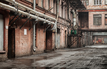 Old industrial street view with red brick facades and tubes