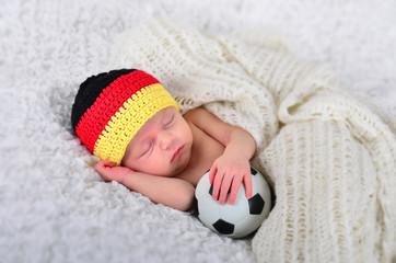 Fototapeta Baby mit Deutschlandmütze und Fußball