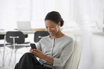 A Woman Seated Checking Her Smart Phone