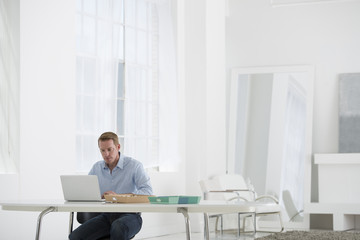 Business. A Man Sitting At A Desk Using A Laptop.