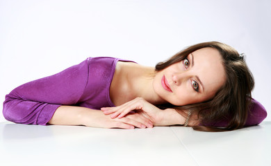 Beautiful woman lying on the table over gray background