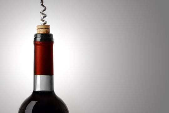 Opening a bottle of red wine, on white background