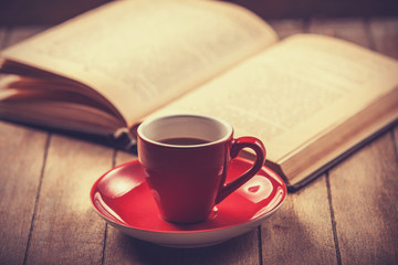 red cup of the coffee and vintage book.