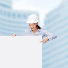 businesswoman in helmet pointing finger to board