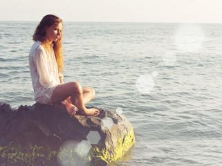 girl sitting on a rock sea