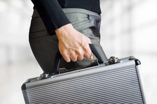 Business woman holding an aluminium briefcase