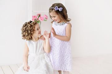 Cute little girls in white dresses talking.