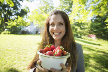 On The Farm. A Woman Carrying A Bowl Of Organic Fresh Picked Strawberries.