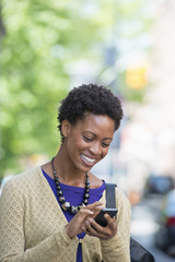 City. A Woman In A Purple Dress Checking Her Smart Phone.
