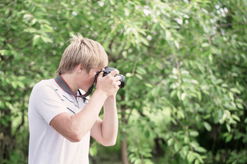 boy with a camera photographs outdoor
