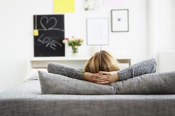 Deutschland, München, Junge Frau entspannt auf der Couch