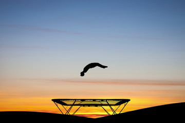 Wall Mural - silhouetted gymnast on trampoline at sunset