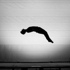 Fototapete - silhouetted man on trampoline