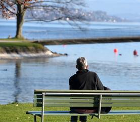 homme de dos  lisant au bord du lac
