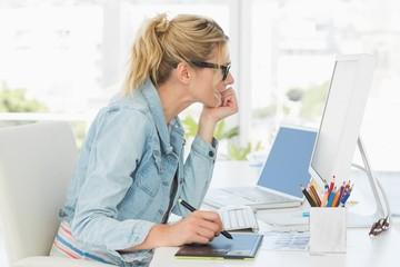Blonde pretty designer using digitizer at her desk