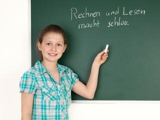 Schülerin schreibt an die Tafel