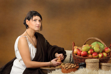Young Romana peeling the onion with basket full of fruits and ve