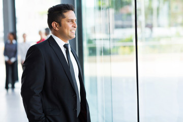 indian businessman looking outside window