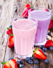 Fresh milk, strawberry and blueberry drinks on wodeen table