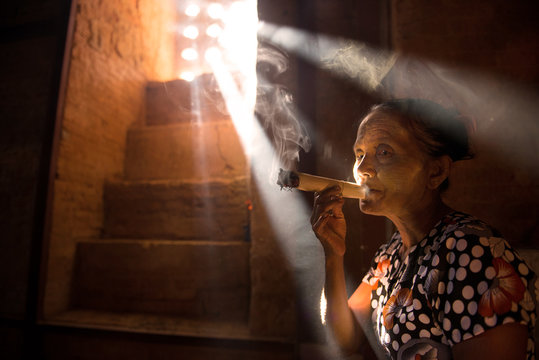 old woman smoking cigars in ancient myanmar temple. dramatic lig