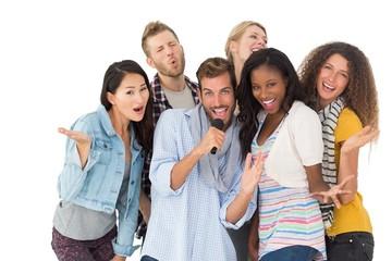 Happy group of friends having fun doing karaoke