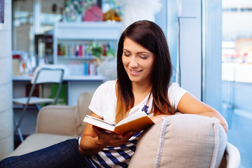Happy woman reading book, sitting on couch