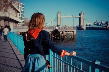 Young woman standing on the bank of the Thames in London