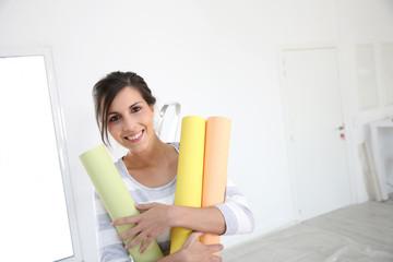 Portrait of cheerful girl holding wallpaper rolls