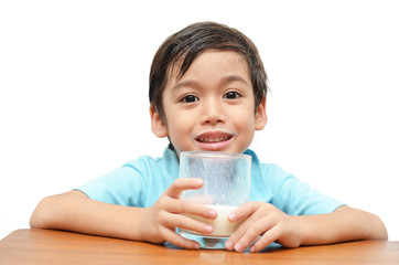Litlle boy holds a glass of fresh milk on a white background