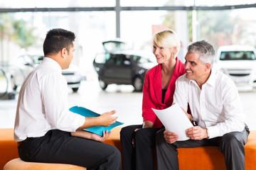 vehicle salesman explaining contract to senior couple