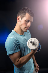 Muscular young man with dumbbells