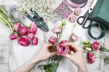 Florist at work. Woman making beautiful bouquet of pink eustoma