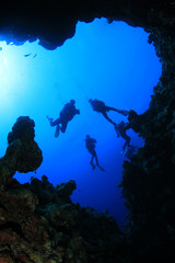 Scuba Divers above underwater cave