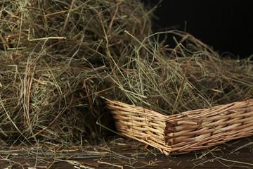 Hay in wicker basket, on dark background