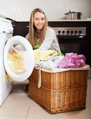 Happy  woman putting clothes in to washing machine