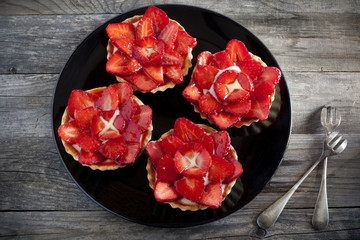 strawberries cakes with pastry cream on plate on wooden table