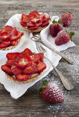 strawberries cakes on white napkin with forks on table