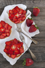 strawberries cakes on white napkin with little forks on table