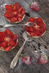 strawberries cakes with pastry cream and icing sugar on table