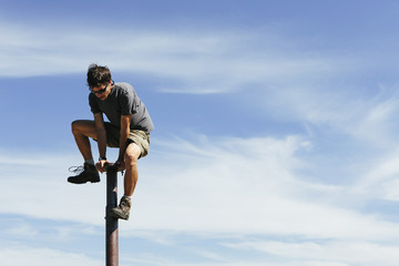 Man climbing on to the top of a metal post, in Surprise Mt, Alpine Lakes Wilderness, Mt. Baker-Snoqualmie NF -