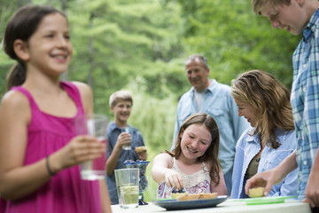 Happy family enjoying party at picnic on organic farm