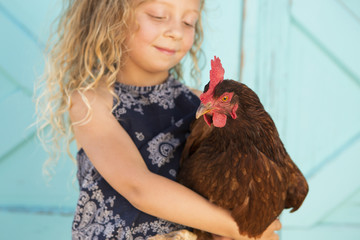 A young girl holding a chicken in her arms.