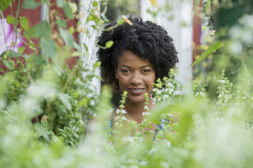 A woman standing in a plant nursery, surrounded by plants, flowers and foliage.