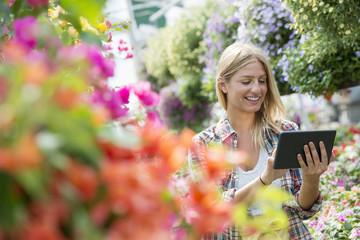 A woman in a plant nursery surrounded by flowering plants and green foliage.
