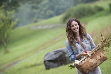 A young woman carrying a basket of freshly harvested garlic and vegetables.