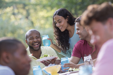 A group of people having a meal outdoors, a picnic. Men and women.