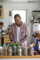 A young man in a kitchen preparing salad leaves and vegetables.