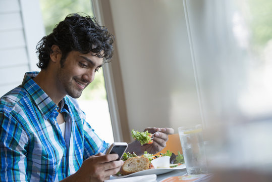 A  man seated checking his phone, and eating in a cafe.