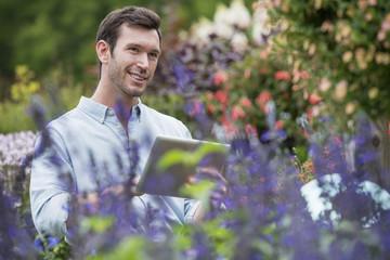 An organic flower plant nursery. A man working, using a digital tablet.